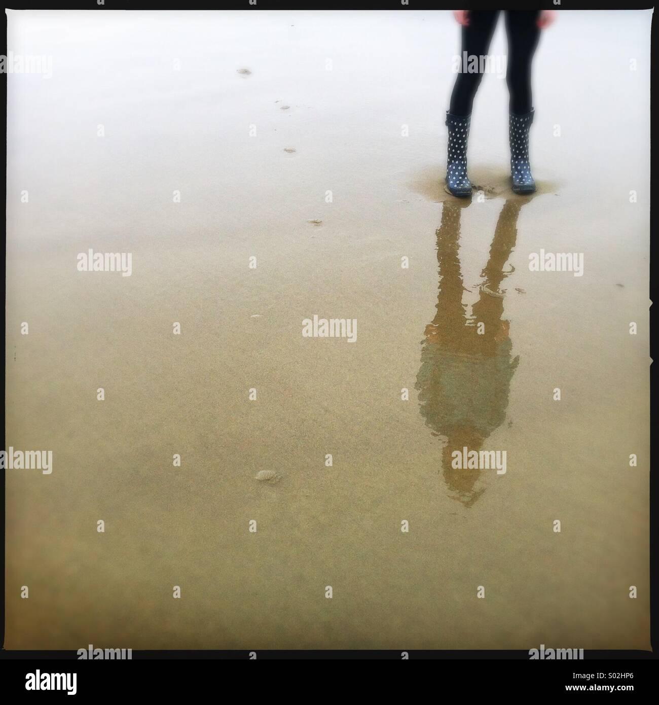 La riflessione della persona in piedi sulla sabbia bagnata Immagini Stock