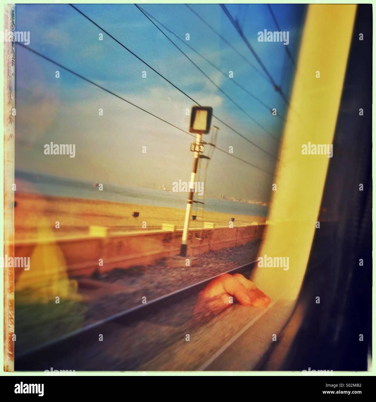 La riflessione di una mano di un giovane ragazzo guardando fuori della finestra del treno a nord della costa di Barcellona, in Catalogna, Spagna Foto Stock