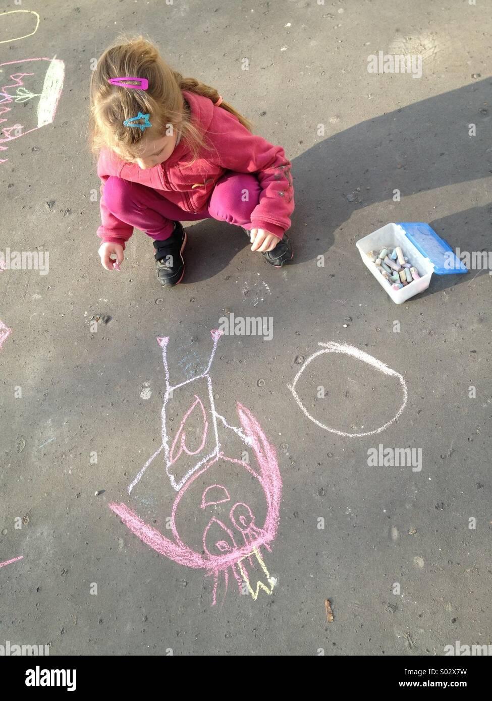 Bambina disegno con gesso su asfalto Immagini Stock