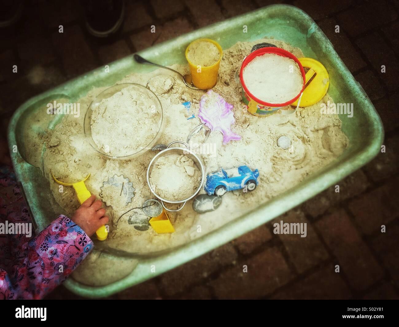 Buca di sabbia, bambino la mano di plastica di contenimento vanga, giocattoli di sabbia Immagini Stock