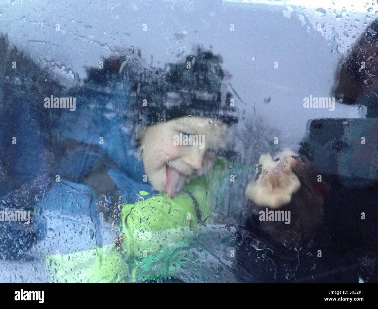 Ritratti di bambini su bagnato finestra nel giorno di pioggia Immagini Stock