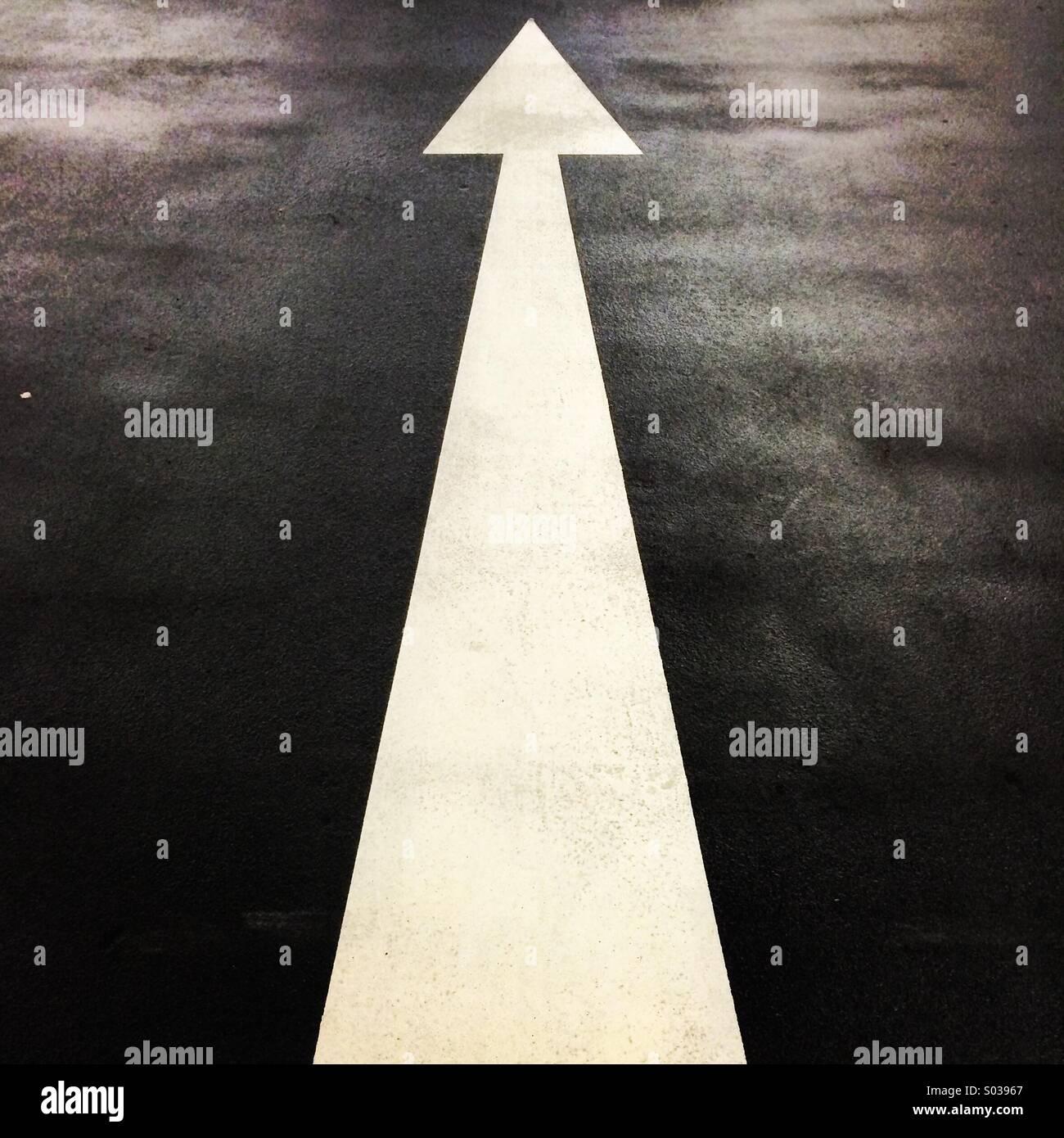 Lungo la freccia bianca verniciata sul asfalto. Immagini Stock