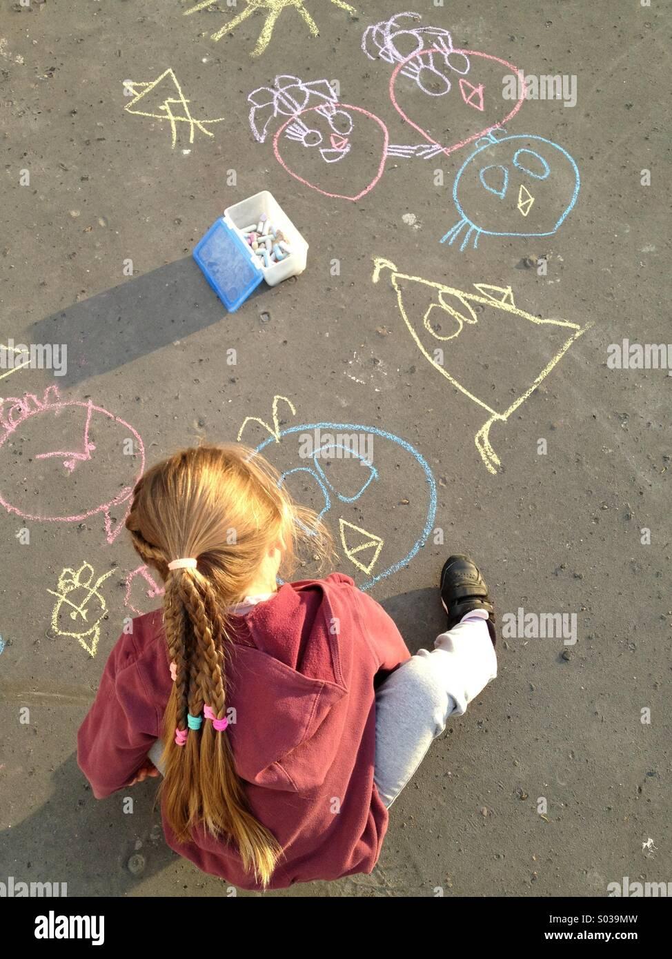 Bambino disegna con un gessetto su asfalto Immagini Stock