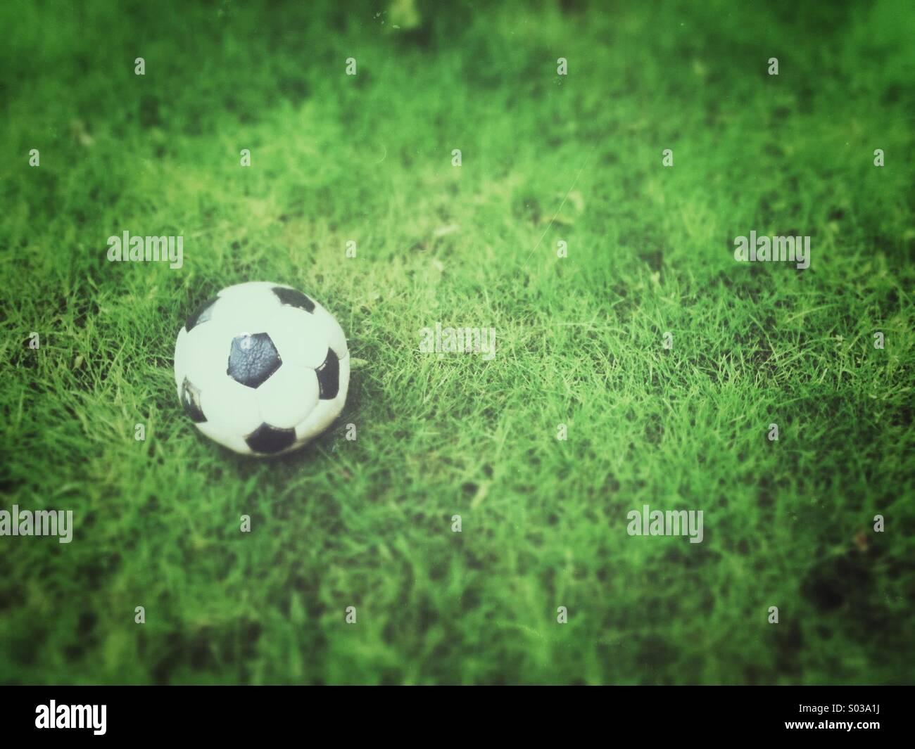 Vecchio calcio, deflazionato sull'erba. Grunge e tilt-shift gli effetti applicati. Immagini Stock
