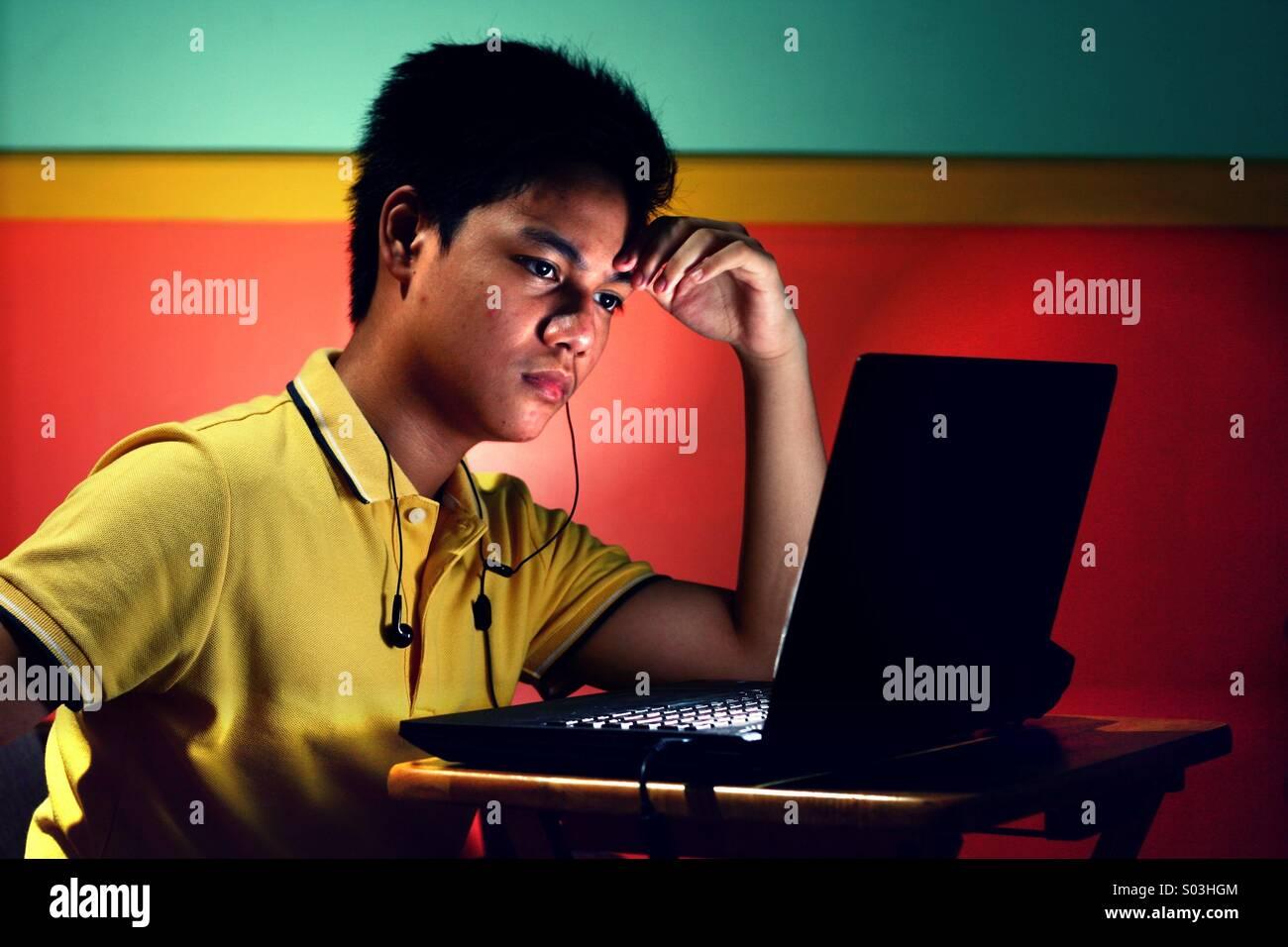 Asian ragazzo adolescente di lavoro o di studio su un computer portatile Immagini Stock