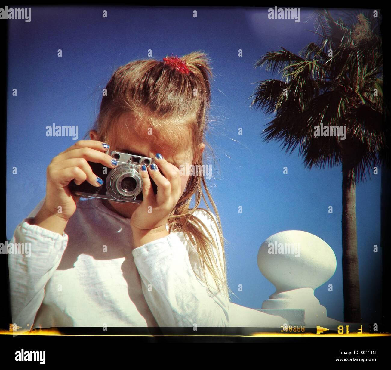 6 anno vecchia ragazza tenendo fotografia con fotocamera vintage. Immagini Stock