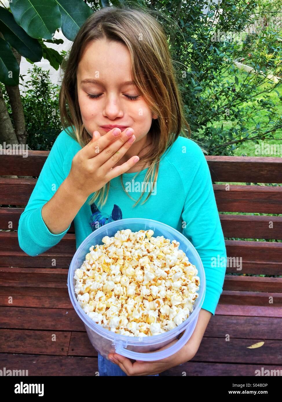 Ragazza giovane mangiare popcorn Immagini Stock