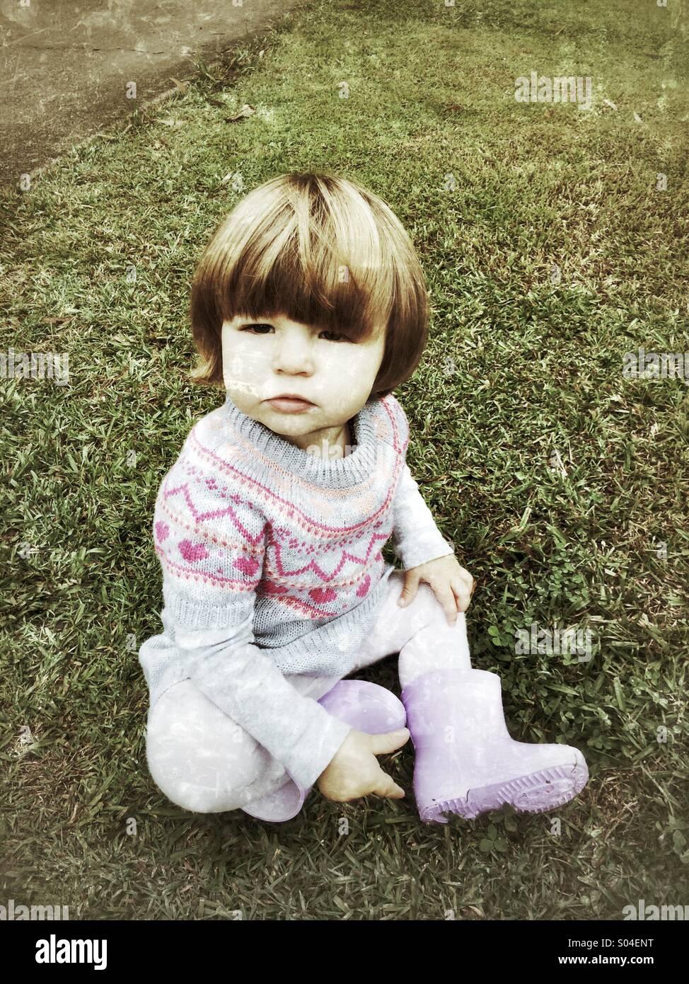 Bambino seduto su erba bagnata con gli stivali da pioggia Immagini Stock
