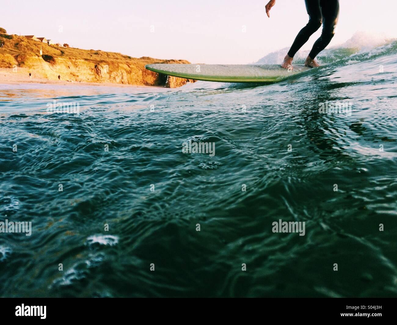 Surfer su un longboard al tramonto in estate Immagini Stock