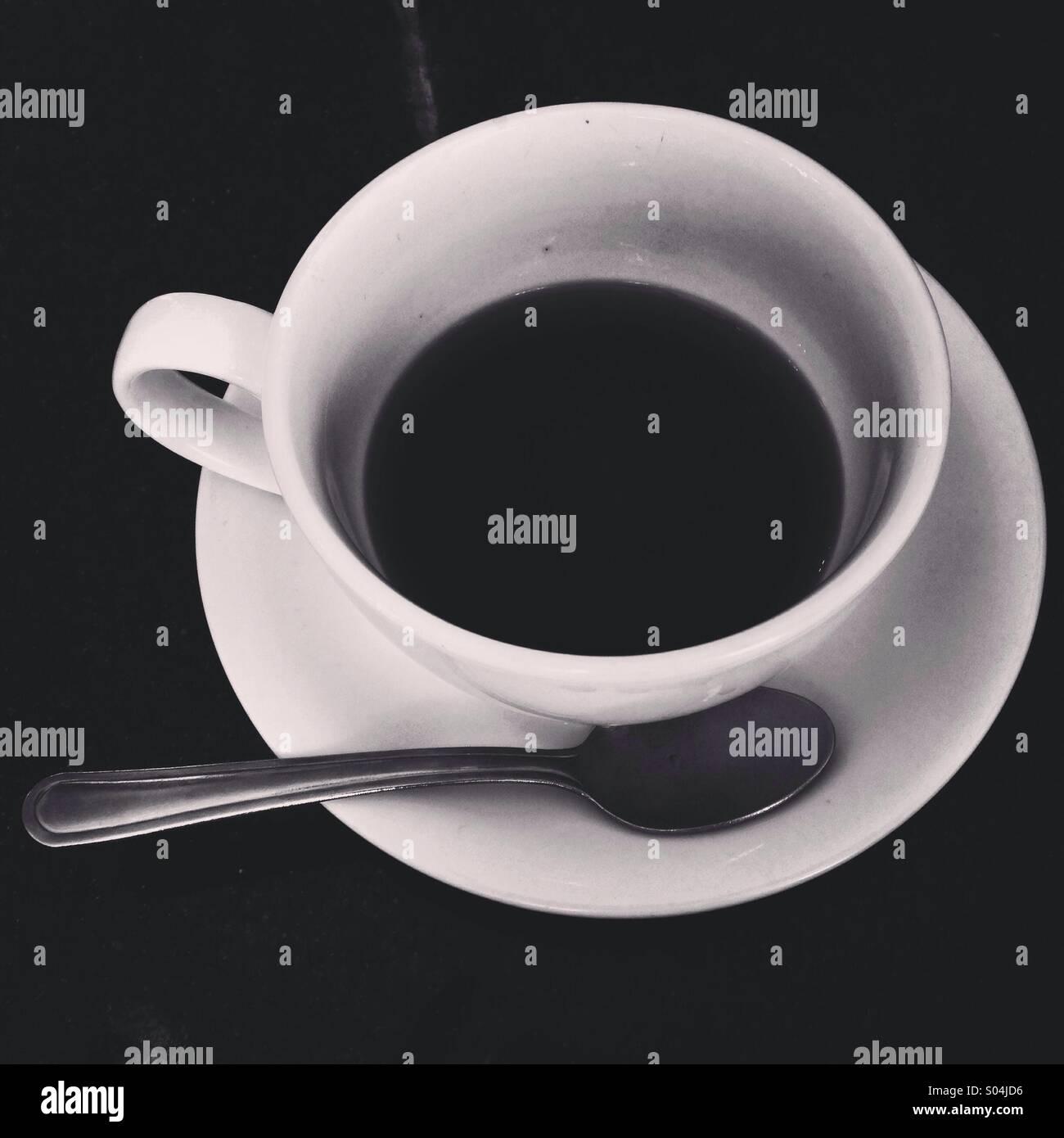 Una tazza e piattino di caffè piena a metà con un cucchiaio Immagini Stock