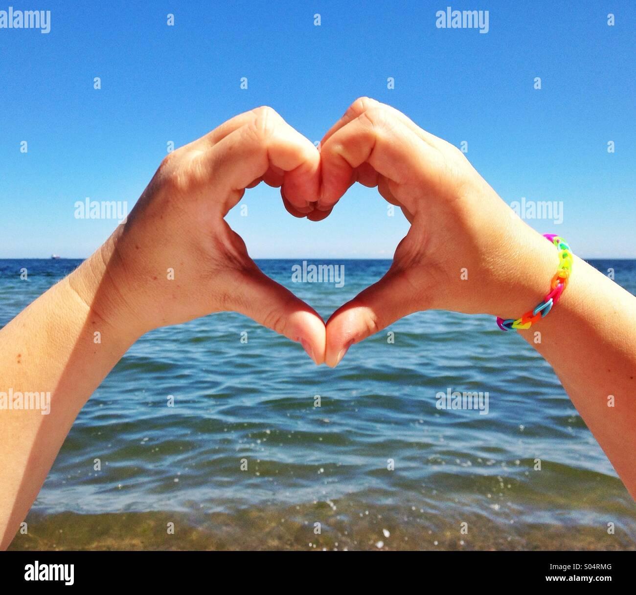 Mani forma di cuore contro il mare Immagini Stock