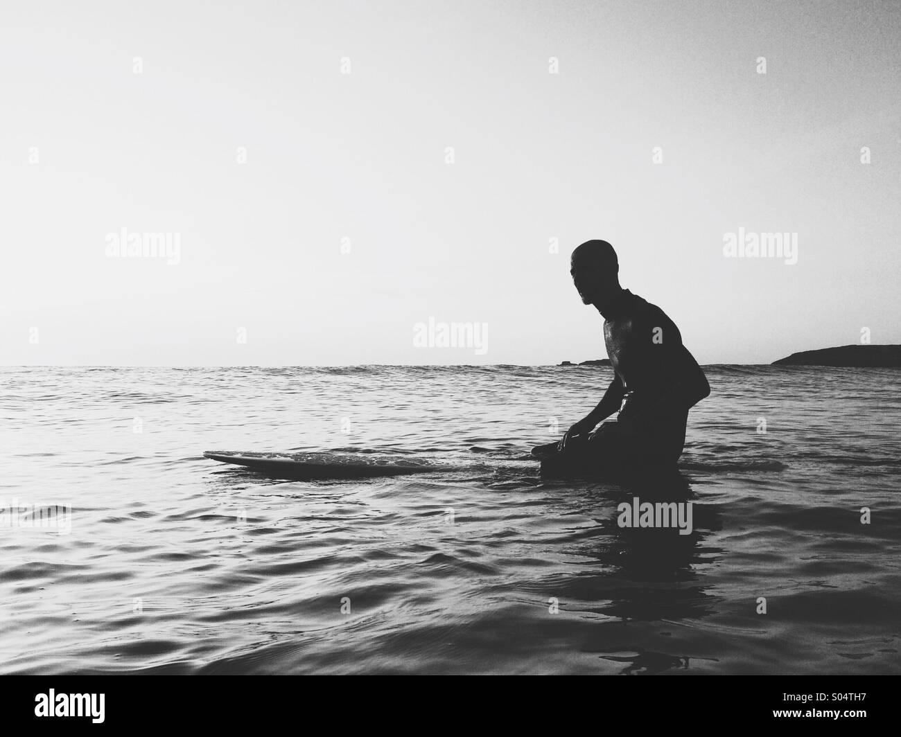 Surfer sulla tavola da surf in attesa di onde. Immagini Stock