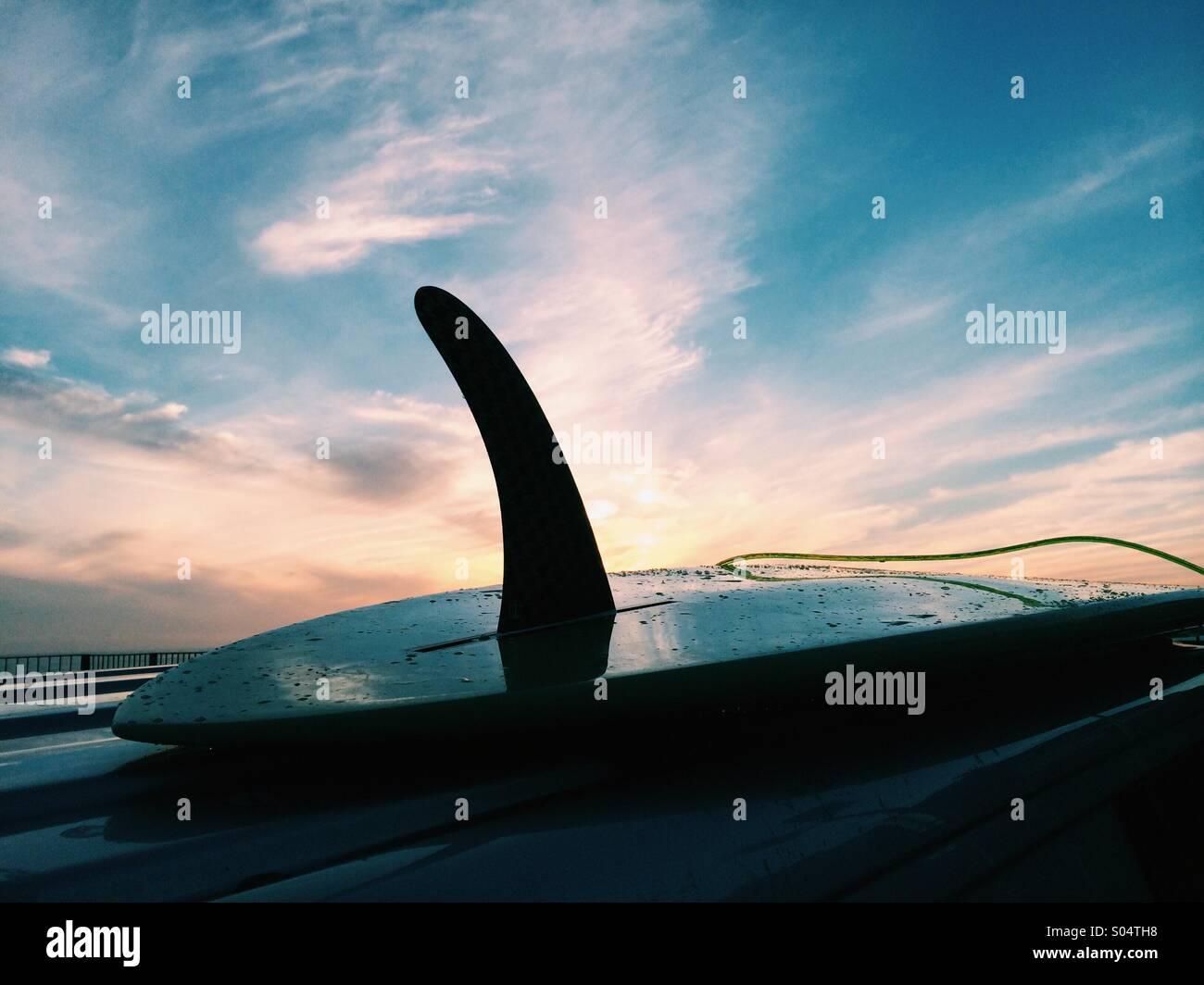 Tavola da surf su un tetto del furgone al tramonto Immagini Stock