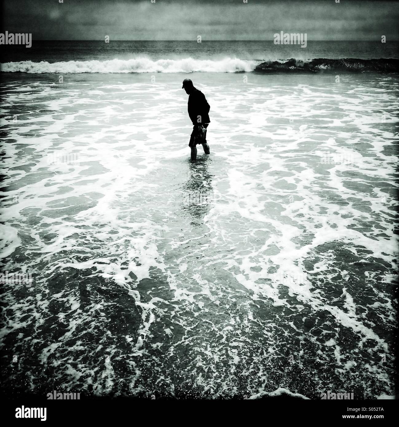 Un uomo cammina nella rottura surf sulla spiaggia Limanture, Pt. Reyes National Seashore. Immagini Stock
