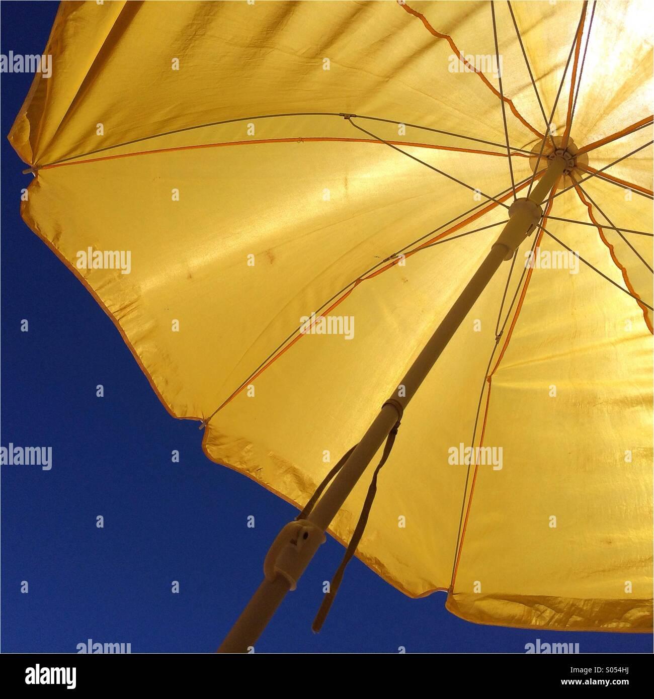 Giallo ombrellone in spiaggia contro il cielo blu Immagini Stock