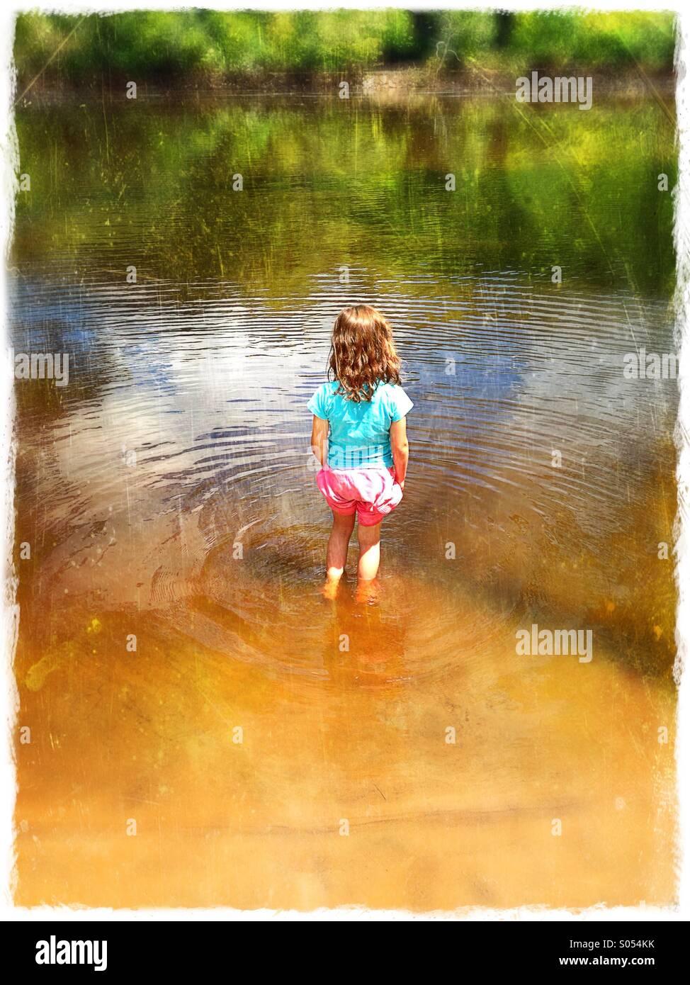 Una bambina in piedi in un fiume, come visto da dietro. Immagini Stock