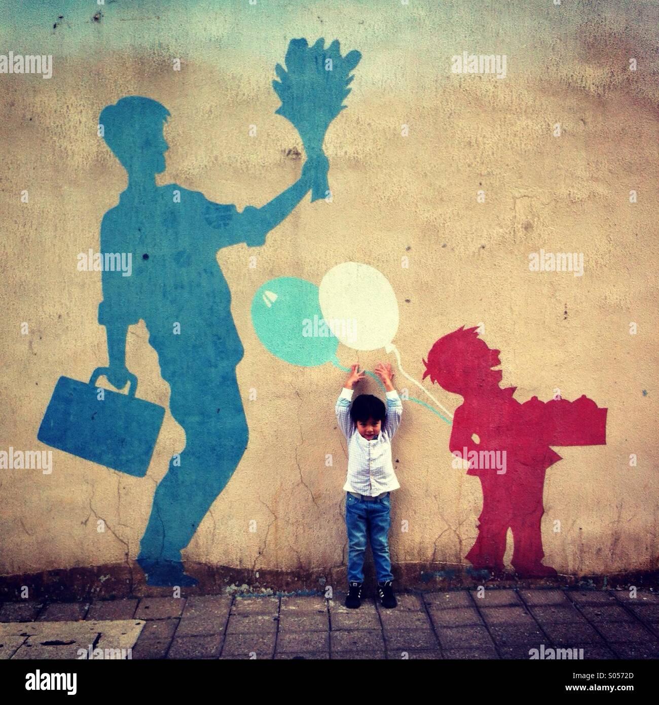 Little Boy di fronte alla fotocamera cerca di raggiungere per il palloncino dipinto sul muro Foto Stock