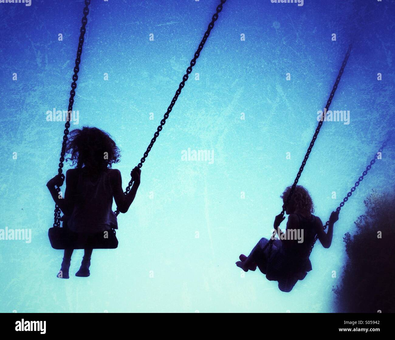 Due ragazze su altalene stagliano contro il cielo blu Immagini Stock