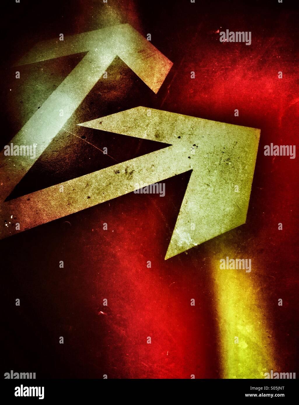 Due frecce dipinte su strada, ogni punta in una direzione diversa. Immagini Stock