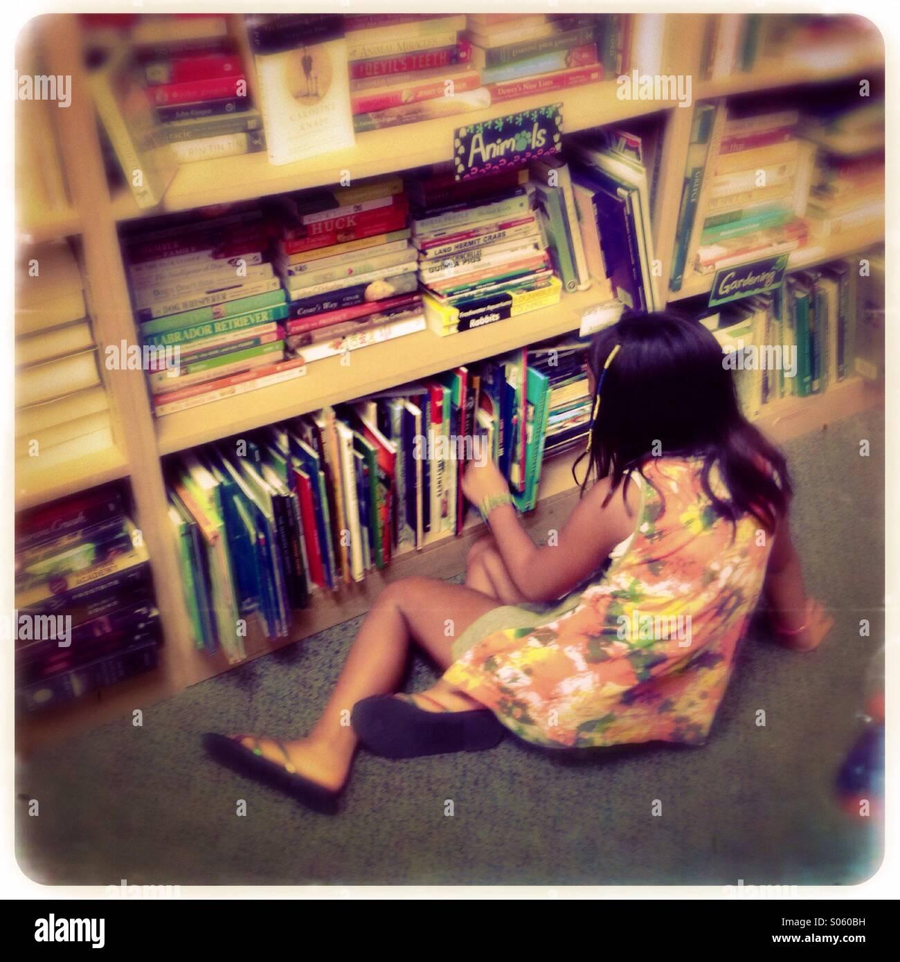 Bambina cerca di prenotare presso un vecchio negozio di libri Immagini Stock