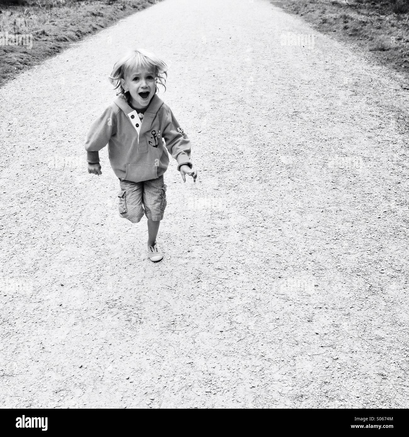 Bambino correre verso di voi, urlando Immagini Stock
