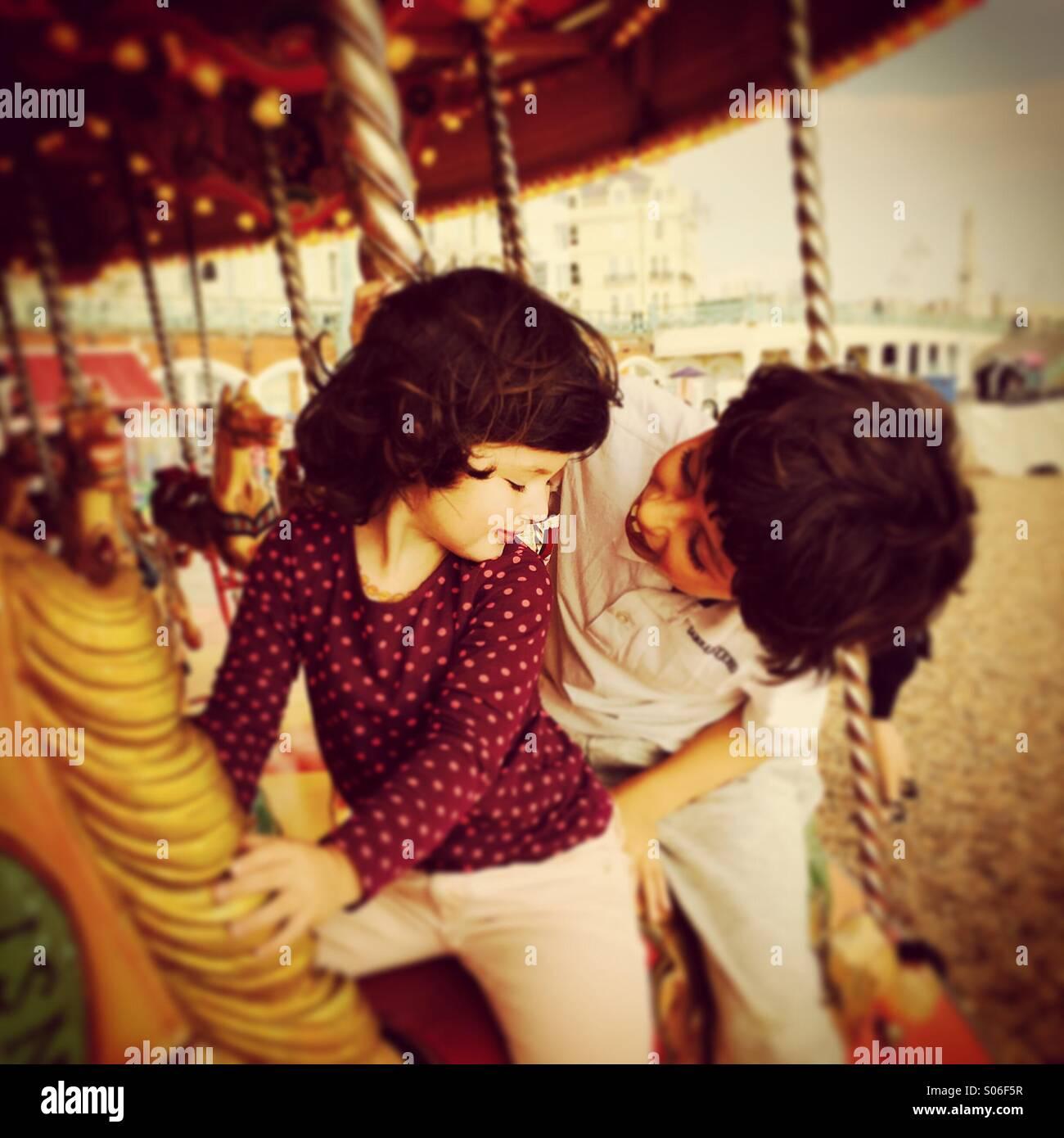 Fratello e Sorella e divertirsi su un merry-go-round / giostra a Brighton, Inghilterra Immagini Stock