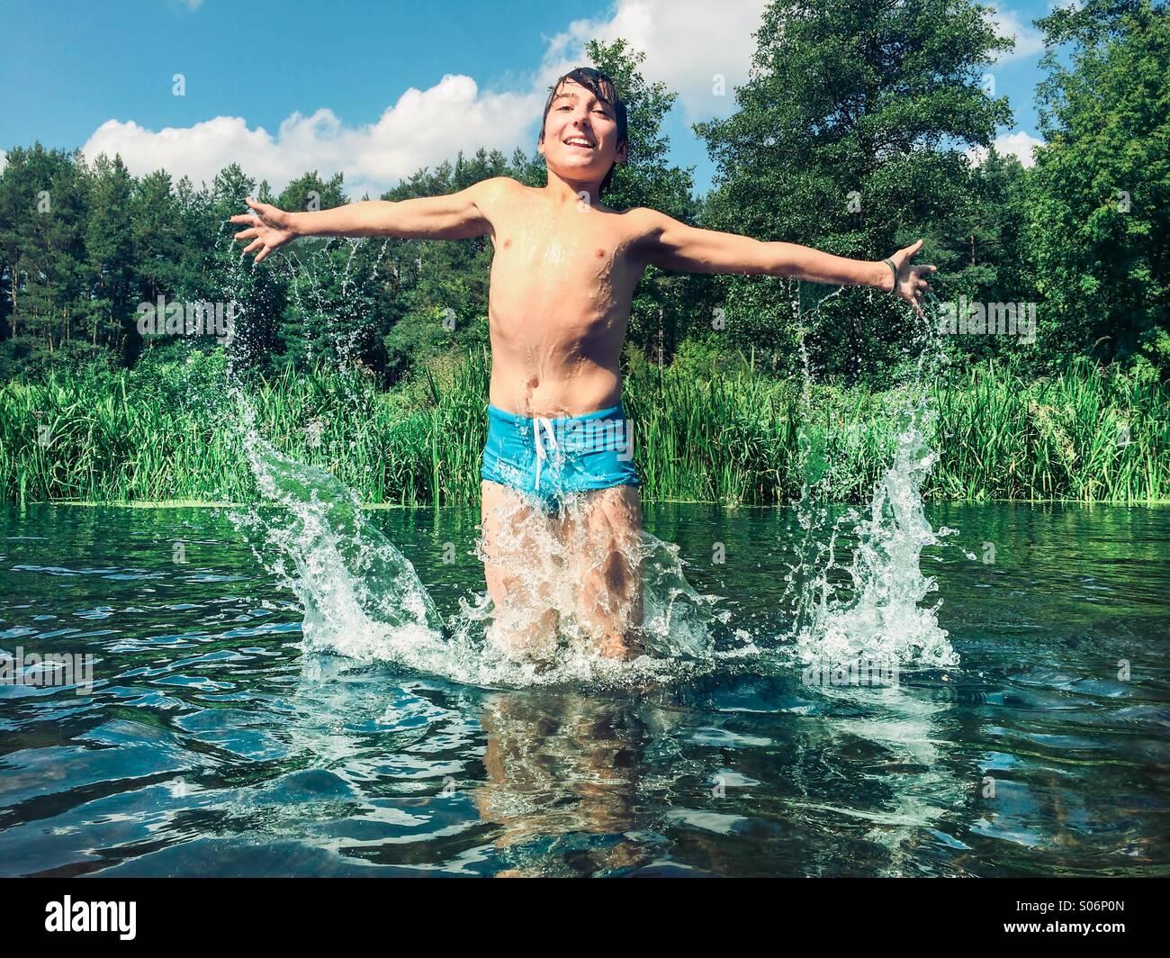Ragazzo giovane schizzi nel fiume Immagini Stock