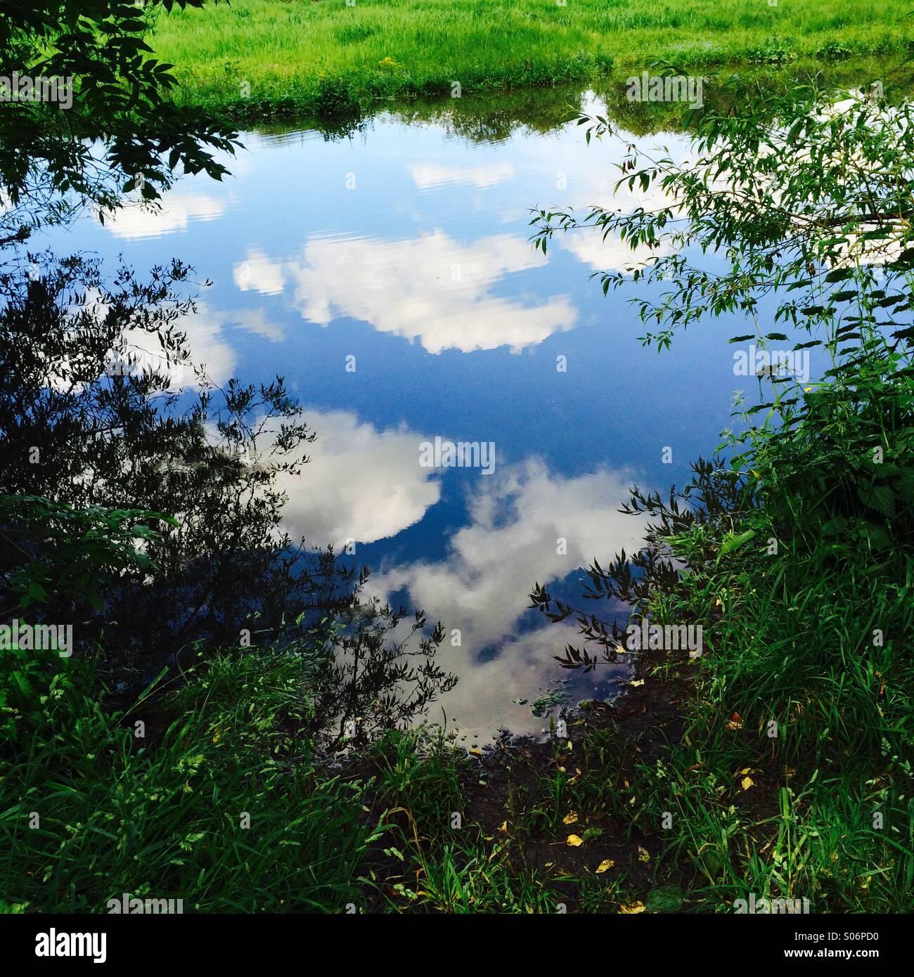 Estate idilliaca scena con nuvole bianche si riflette nel fiume. Immagini Stock