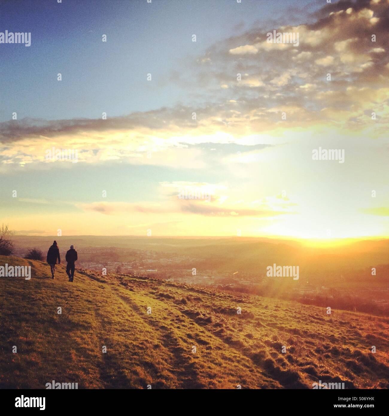 Distante walkers prendendo una Domenica nel tardo pomeriggio passeggiata come il sole proietta raggi oltre la periferia Immagini Stock