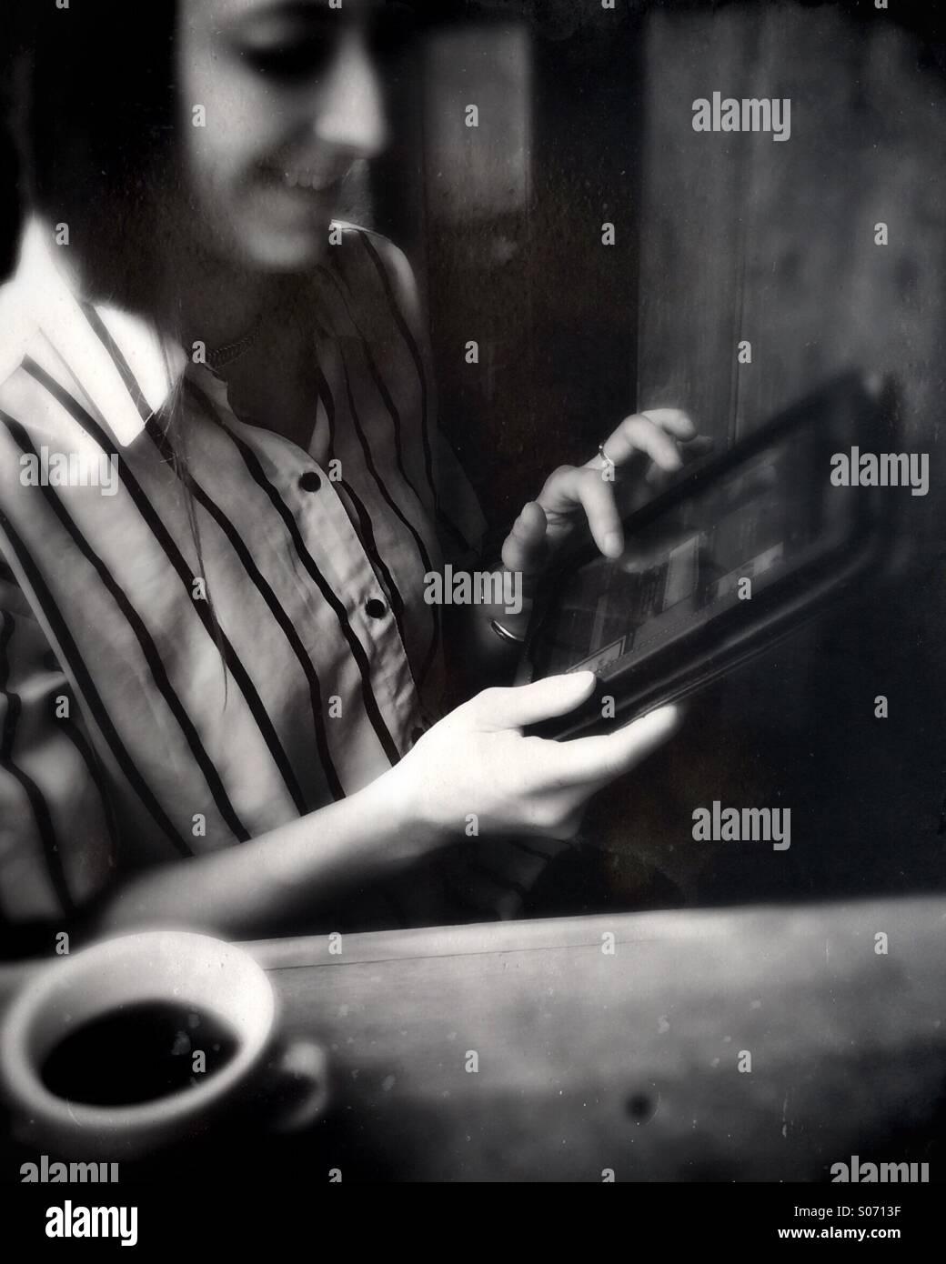 Una giovane donna che utilizza un computer tablet Immagini Stock