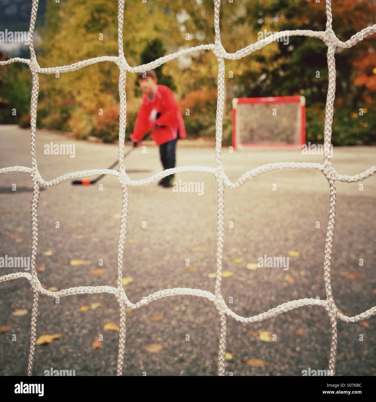 Giovane ragazzo giocando street hockey Immagini Stock