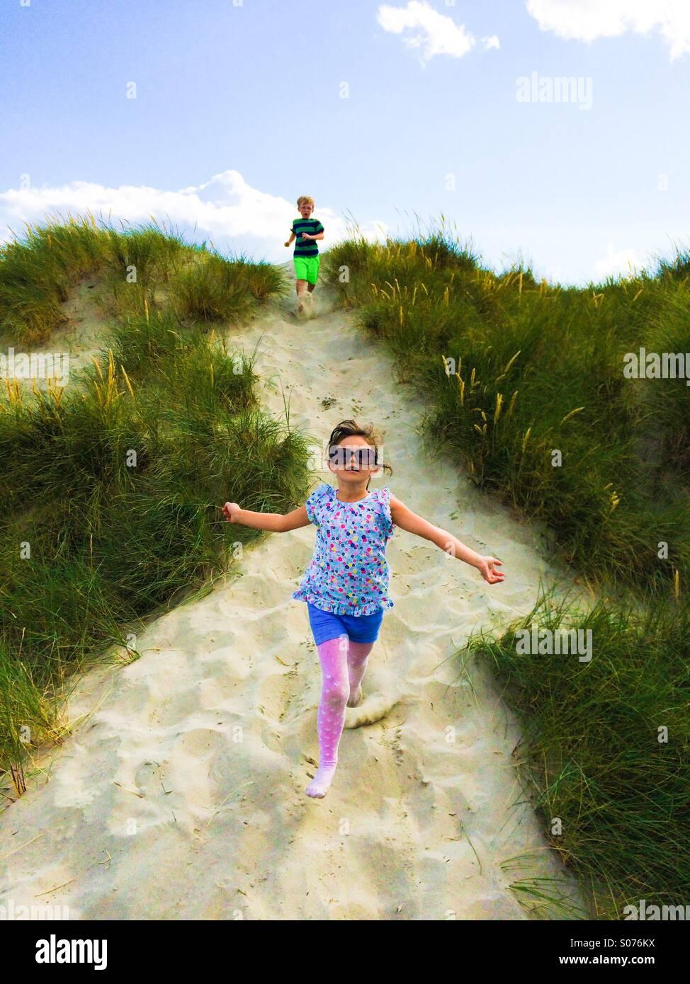 Due cinque anni di bambini che giocano in dune di sabbia Immagini Stock