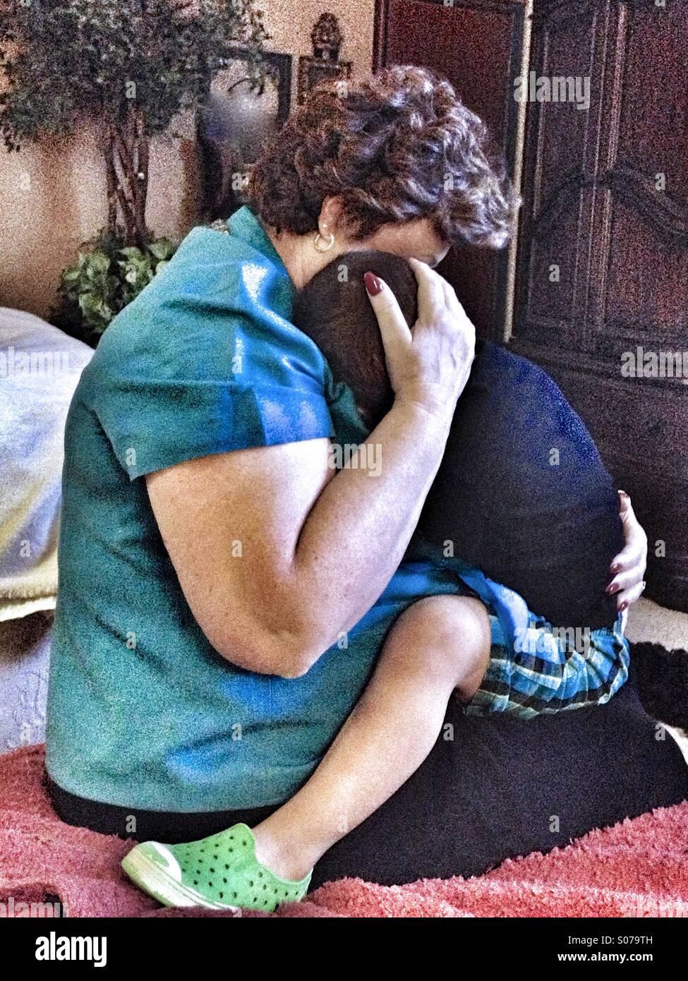 Toccare il colpo di una nonna holding, avvolgente e consolante un ragazzino. Immagini Stock