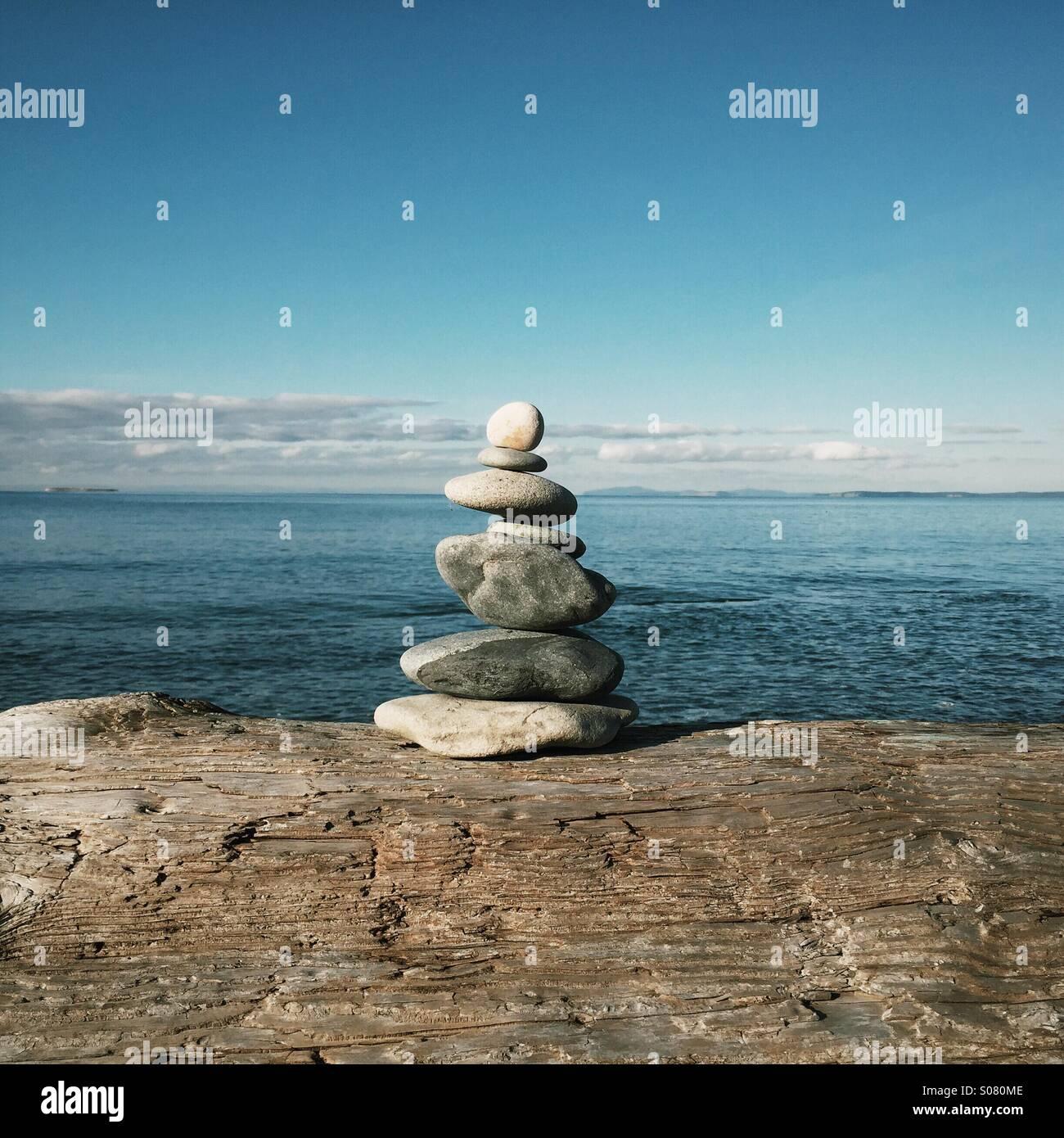 Il tumulo di impilati o pietre equilibrata seduti sul driftwood presso la spiaggia. Immagini Stock