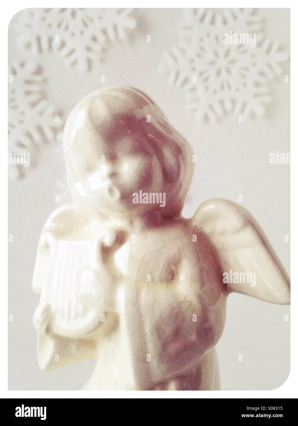 Un angelo Natale figurine con un fiocco di neve sullo sfondo. Foto Stock