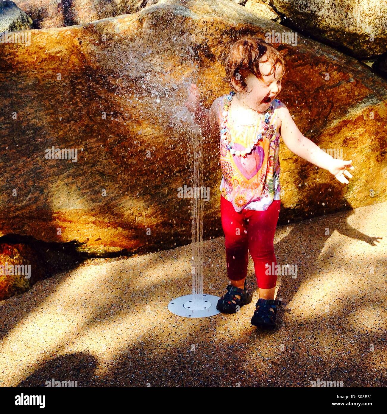Bambina allo splash pad Immagini Stock