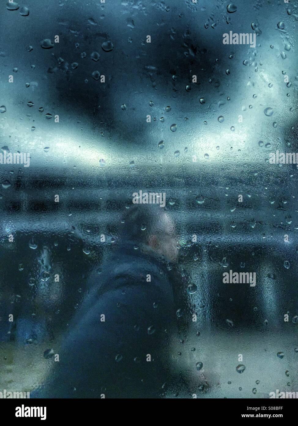 Uomo che corre sotto la pioggia Foto Stock