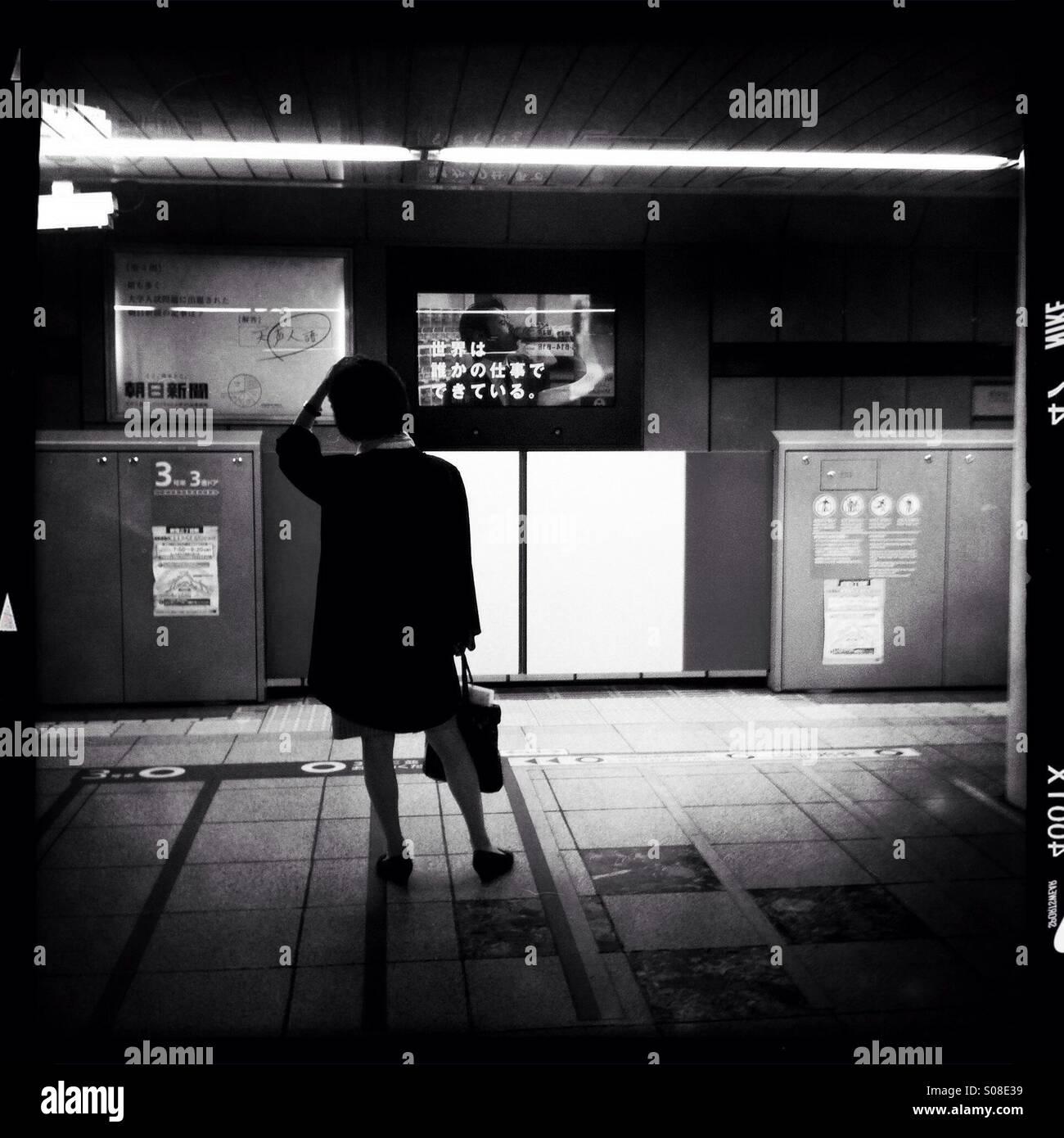 Una donna che aspetta un treno in arrivo a Tokyo metro a