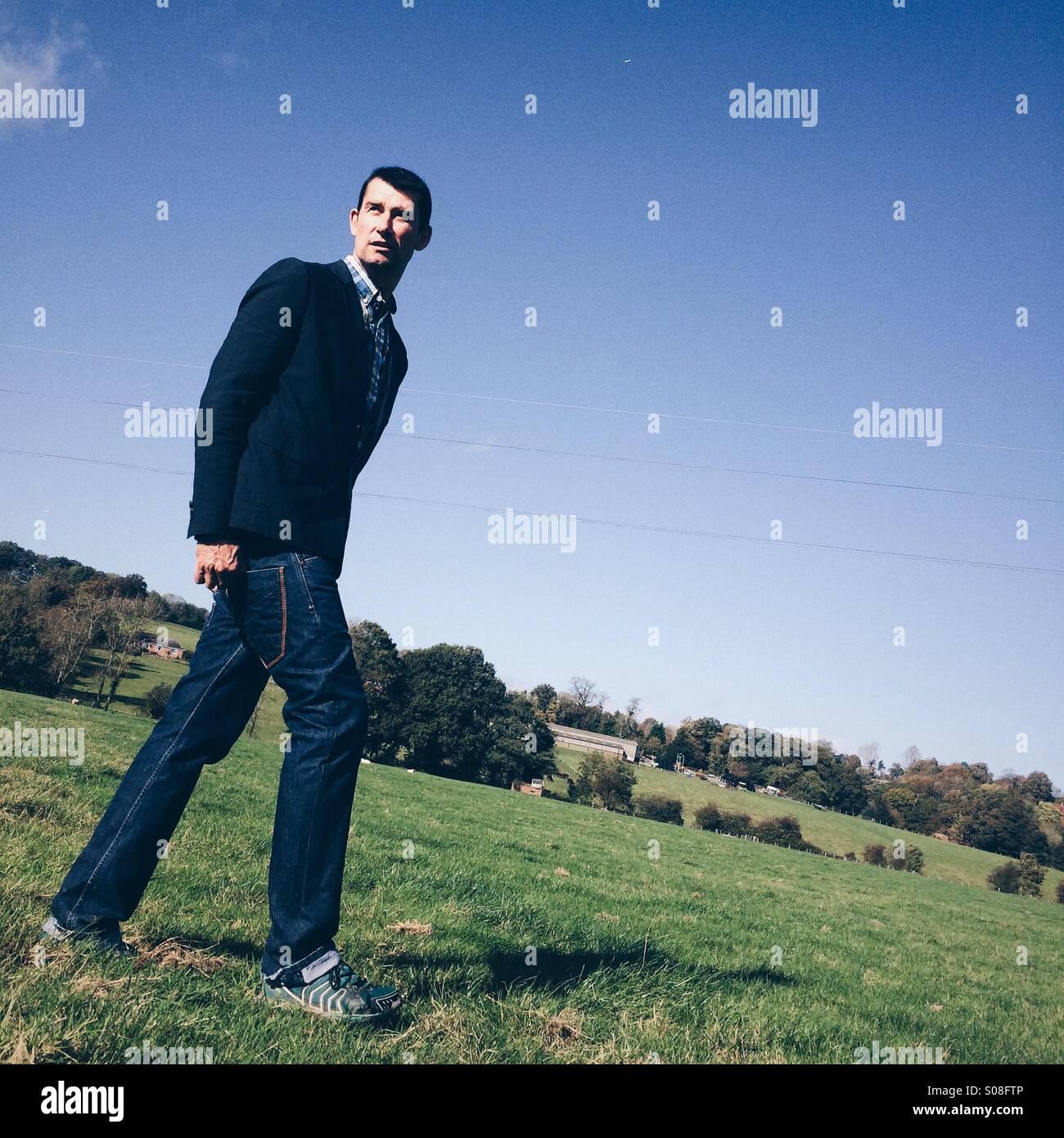 Uomo che cammina in campagna, vestito casualmente in jeans e una giacca. Immagini Stock