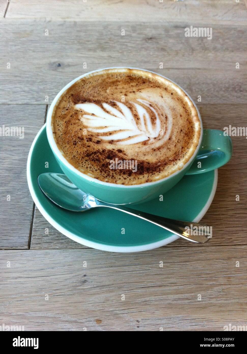 Una tazza di latte con arte sulla sommità di esso Immagini Stock