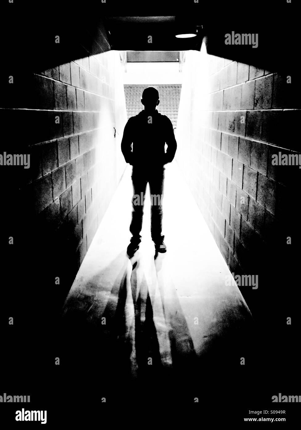 Silhouette di un ragazzo che sta in arena con tunnel di luce da dietro. Immagini Stock