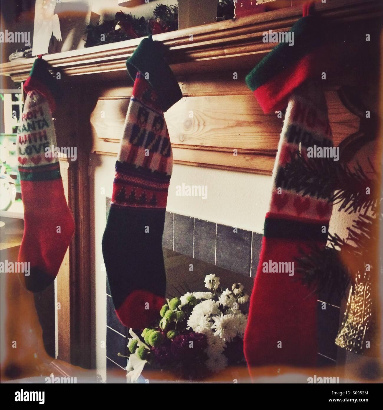 Calze di Natale appeso sopra un caminetto Immagini Stock