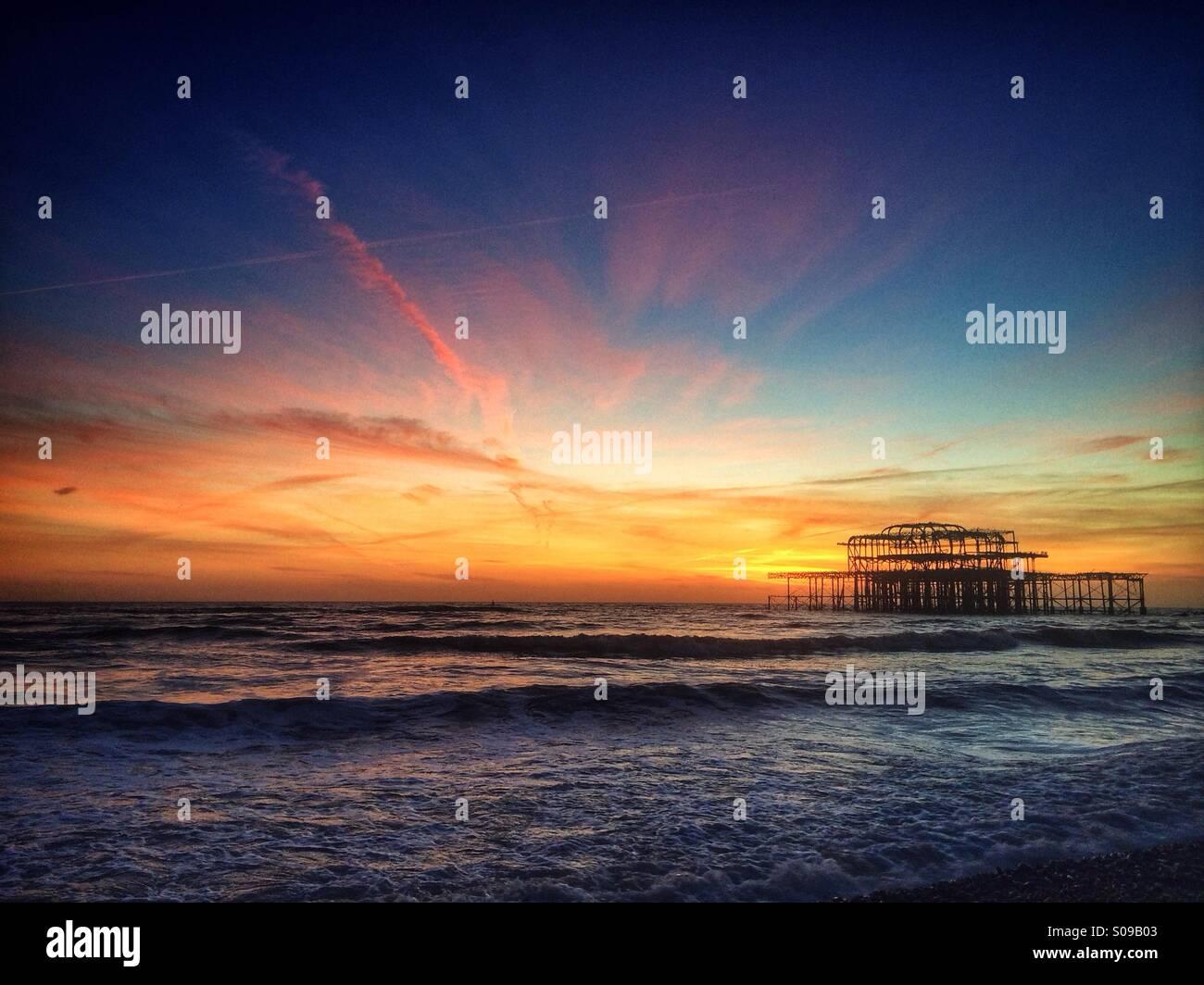 La bruciata rimane di Brighton il Molo Ovest al tramonto, in Brighton, Inghilterra, Regno Unito. Immagini Stock