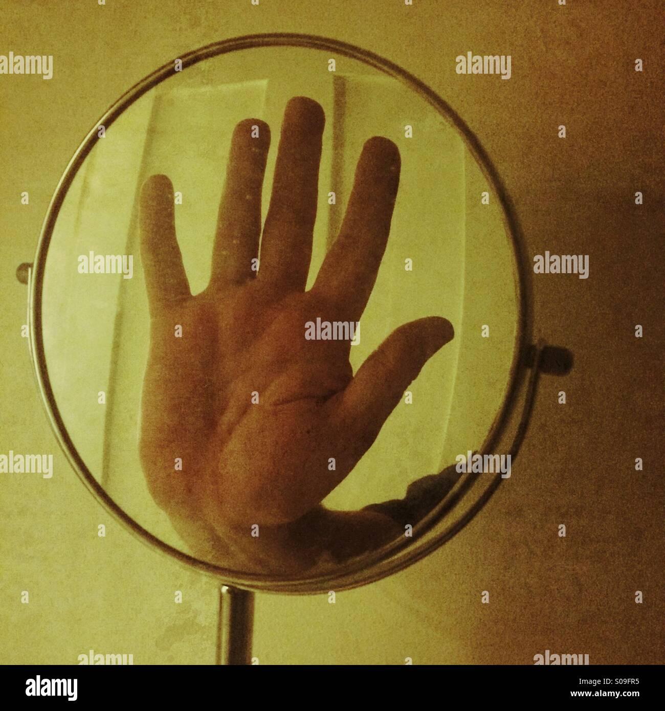 Un riflesso di una mano in un piccolo specchio Immagini Stock