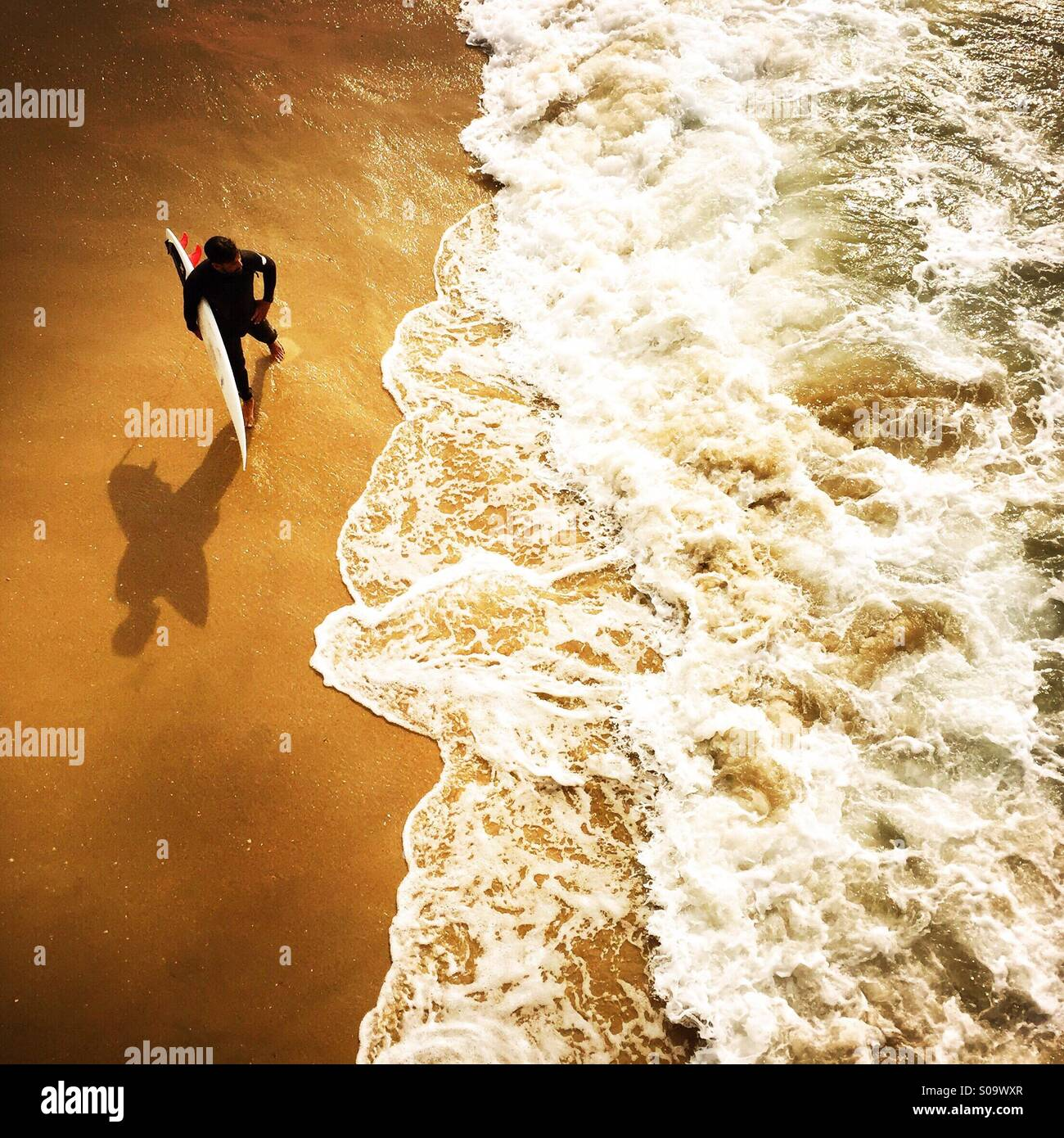 Un surfista attende al litorale di surf. Manhattan Beach, California USA. Foto Stock