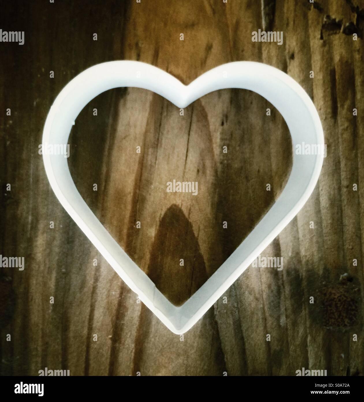 Bianco a forma di cuore formina sul tagliere di legno Foto Stock