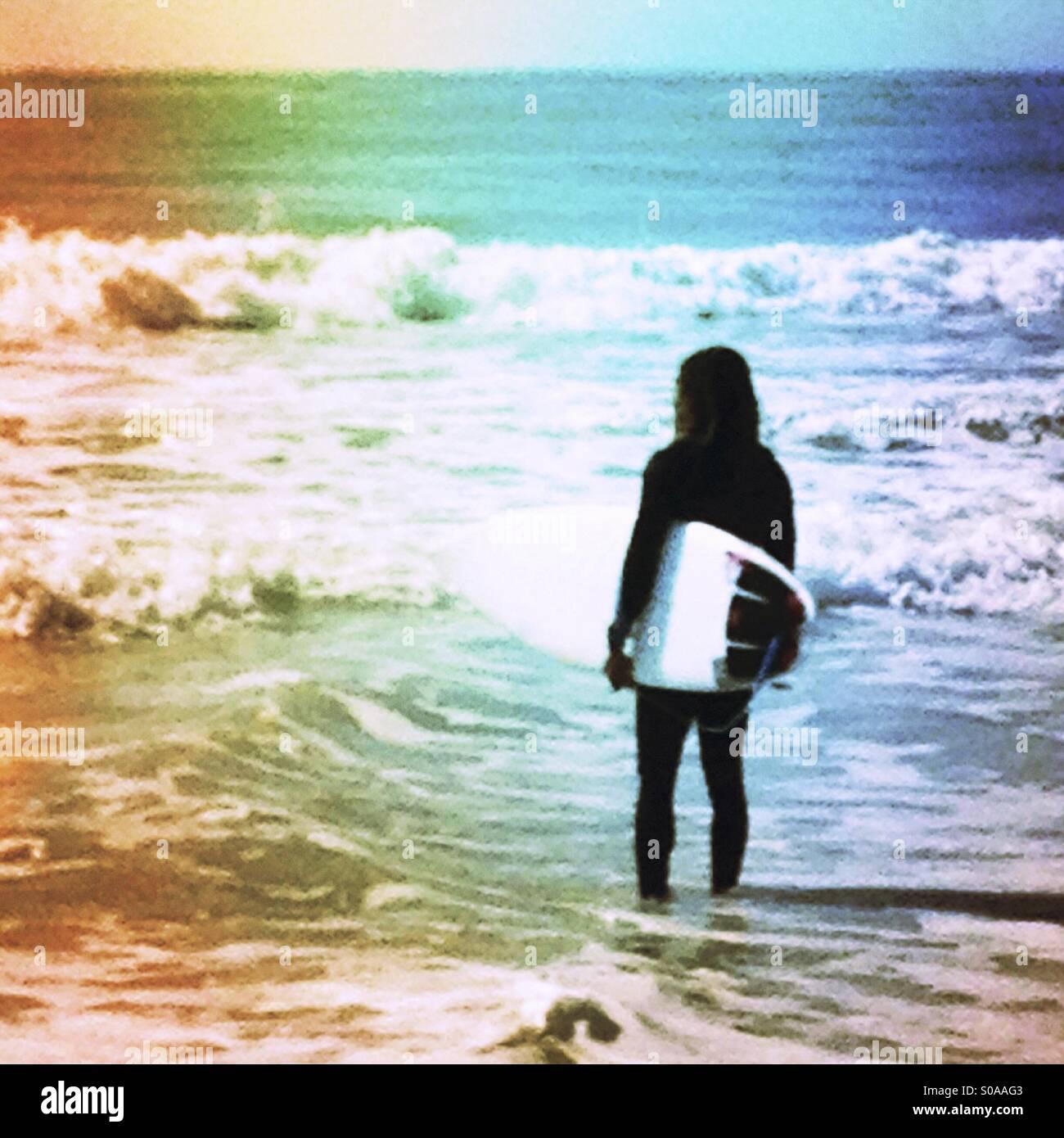 Surfer a guardare il mare e le onde per fare surf. Immagini Stock
