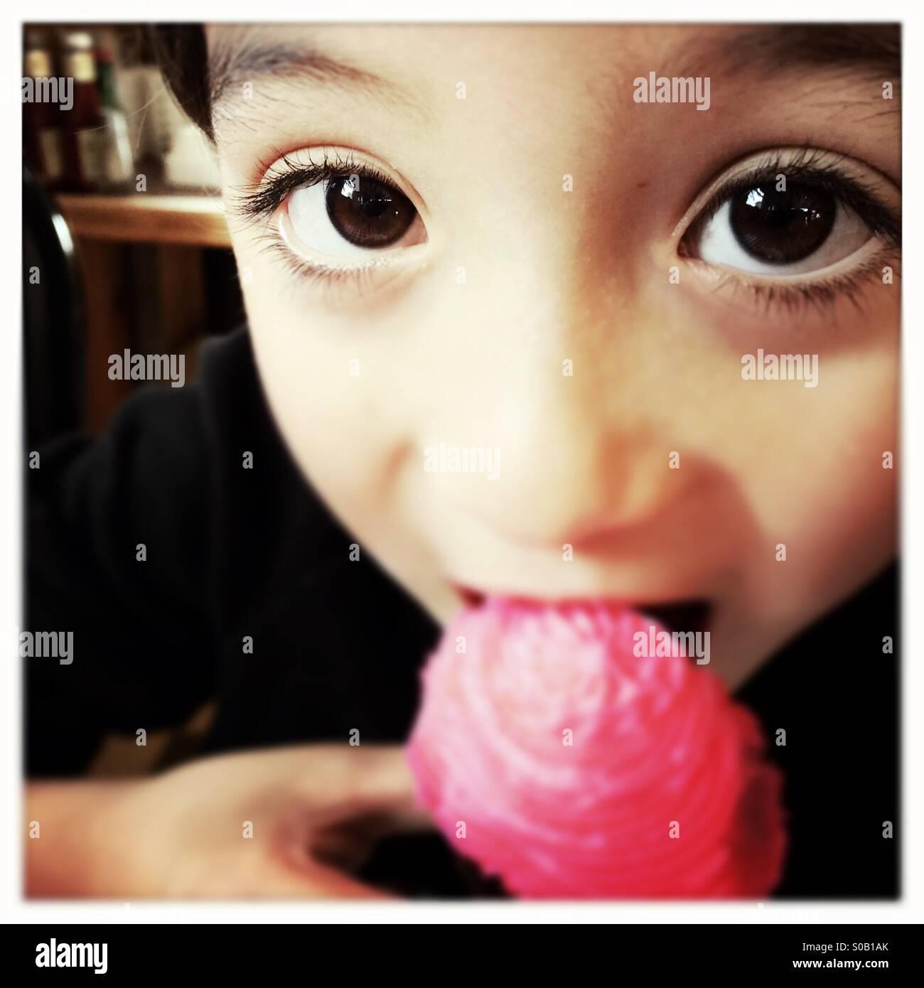 Un bambino di sei anni Asian Caucasian razza mista ragazzo prende un morso di una tortina. Immagini Stock