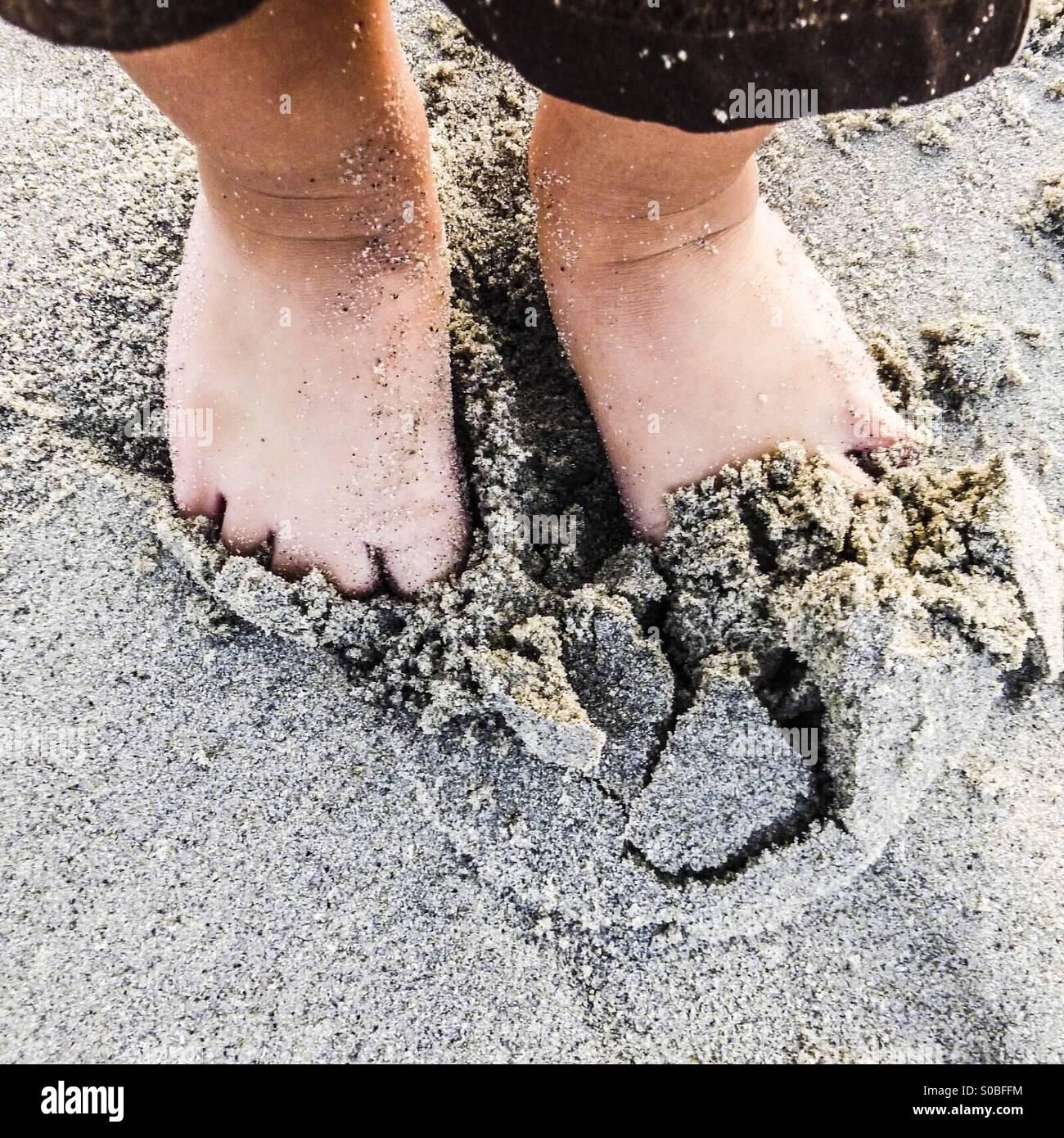 Bambino di scavare i piedi nella sabbia in spiaggia Foto Stock