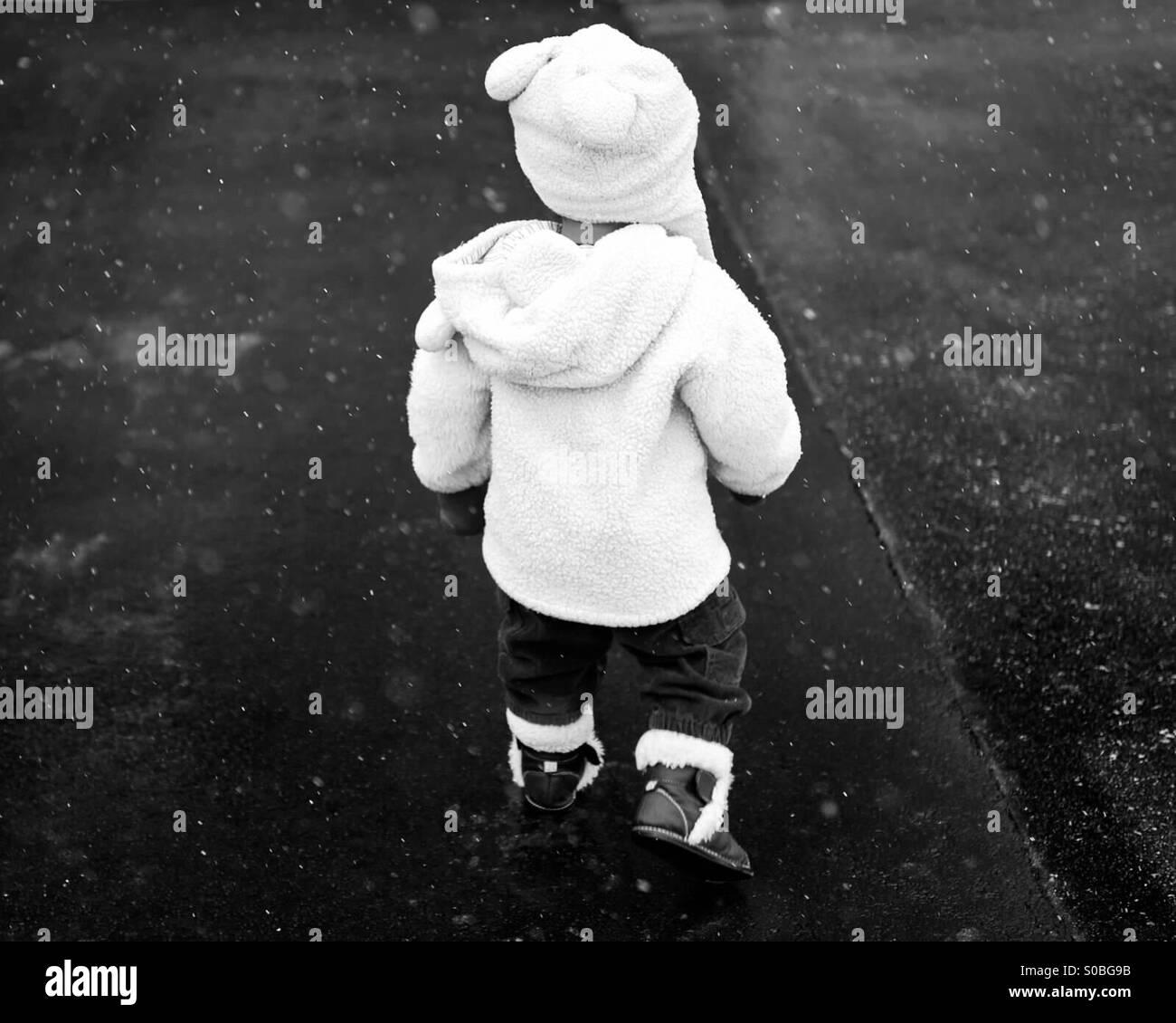 Un bambino a piedi nella neve di luce Foto Stock